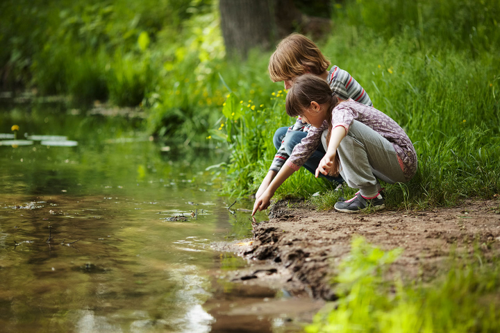 Green Image kids playing in a creek