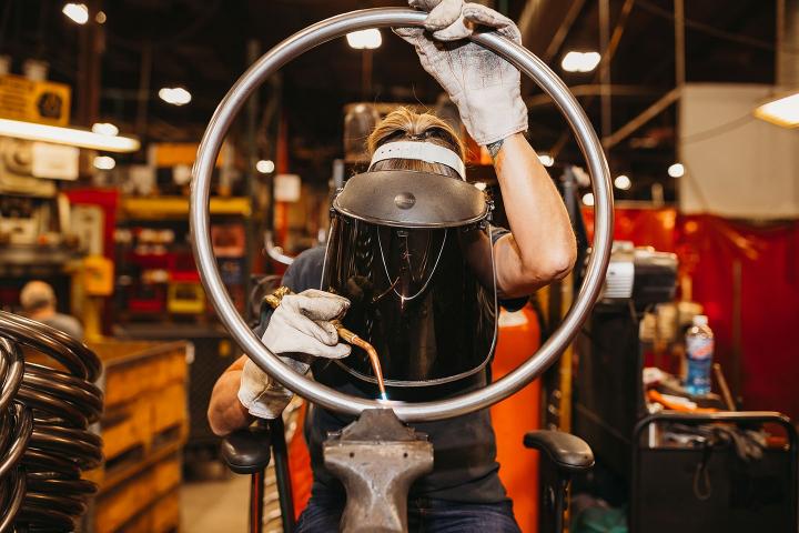 female BioFit welder looking through a steel footring as she welds it
